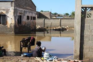Una bambina lava le stoviglie dopo l'alluvione