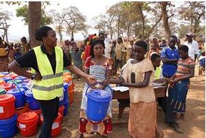 """Ndiyokubwayo, profuga burundese fuggita in Tanzania a causa dei disordini in atto nel proprio Paese, riceve il """"dignity pack"""", un kit igienico (saponi, salviette, assorbenti), che Plan International ha distribuito a donne e ragazze per offrire un minimo di agio. In copertina: Mary-Joseph, una giovane donna di 23 anni, che vive in un campo profughi nei pressi dell'aeroporto di Pibor, Stato di Jonglei, Sud Sudan"""